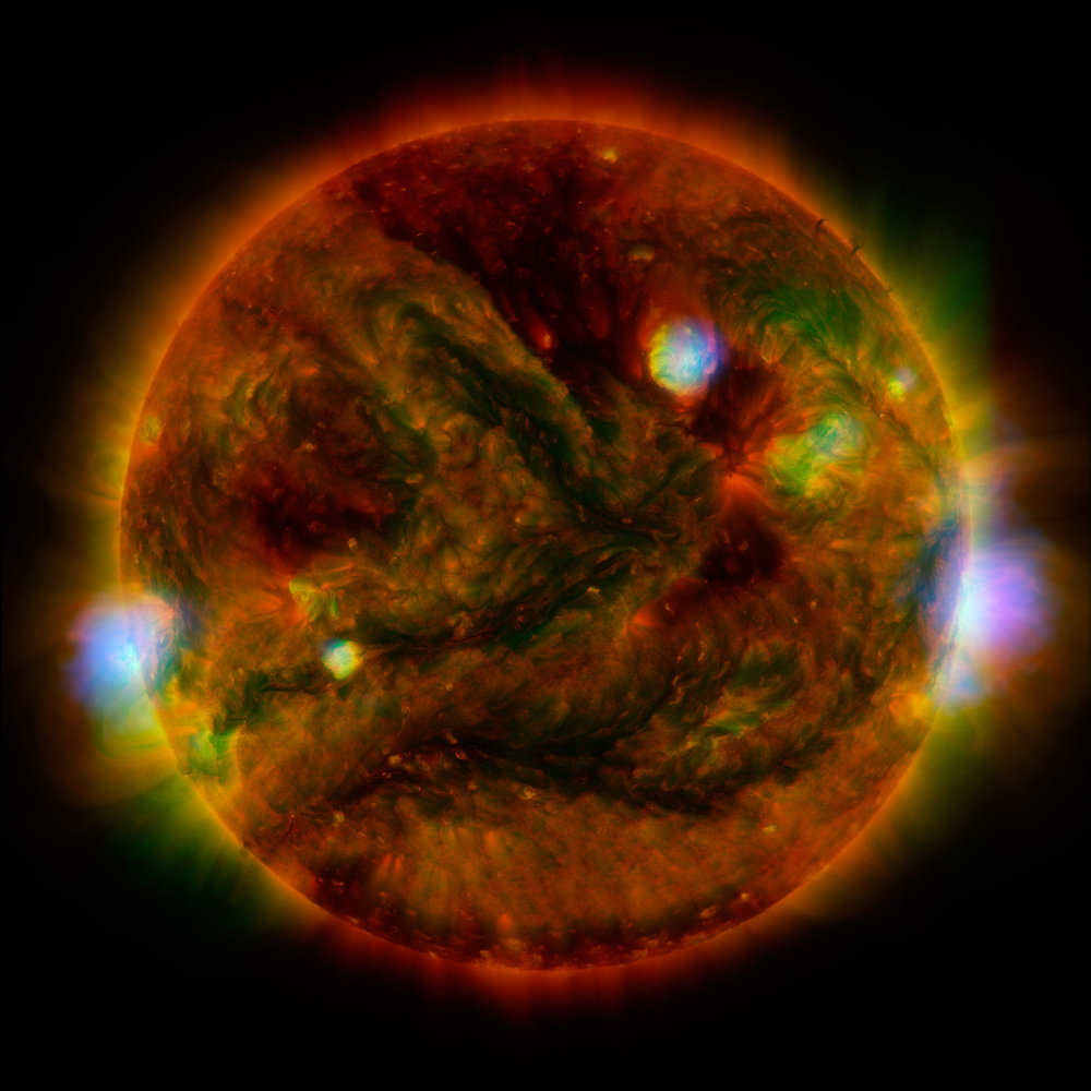 Flaring, active regions of our sun are highlighted in this new image combining observations from several telescopes. High-energy X-rays from NASA's Nuclear Spectroscopic Telescope Array (NuSTAR) are shown in blue; low-energy X-rays from Japan's Hinode spacecraft are green; and extreme ultraviolet light from NASA's Solar Dynamics Observatory (SDO) is yellow and red. Image credit: NASA/JPL-Caltech/GSFC/JAXA