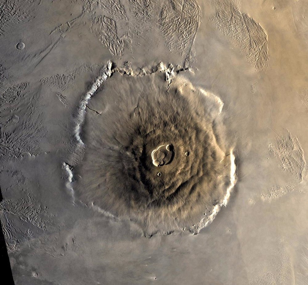 Color mosaic of Olympus Mons volcano on Mars from the Viking 1 Orbiter. The mosaic was created using images from orbit 735 taken 22 June 1978. Olympus Mons is about 600 km in diameter and the summit caldera is 24 km above the surrounding plains. Image credit:  NASA/JPL