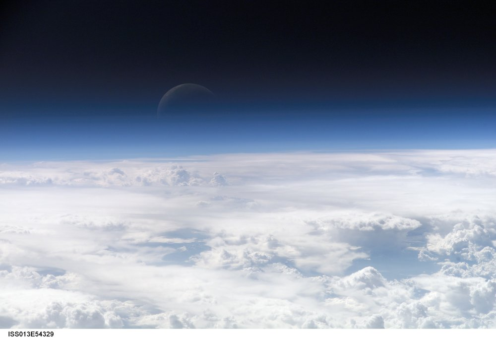 At higher and higher altitudes, the Earth's atmosphere becomes so thin that it essentially ceases to exist. Gradually, the atmospheric halo fades into the blackness of space. This astronaut photograph captured on July 20, 2006, shows a nearly translucent moon emerging from behind the halo. Image credit:  NASA