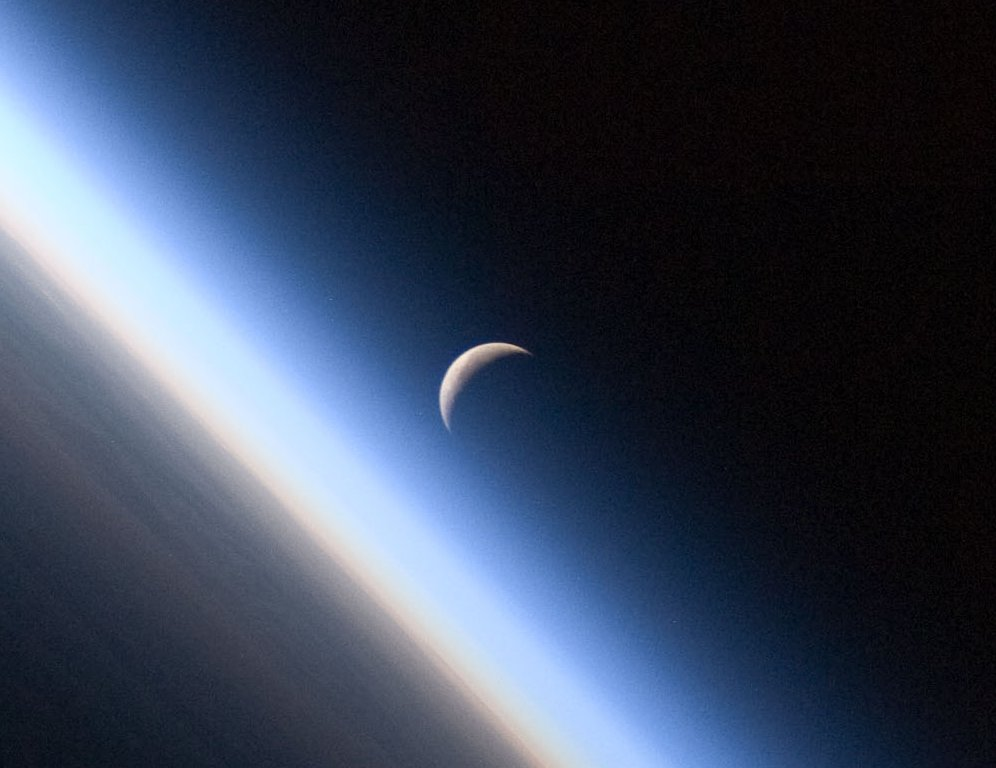 A setting, waning crescent moon amid the thin line of Earth's atmosphere. Image credit:  NASA