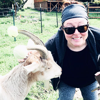 Lisa Osborne and a new goat yoga friend (tennis balls on his horns are  for safety not sport ).