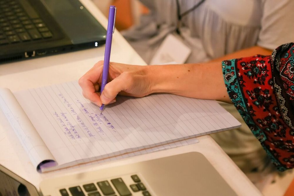 Laptop open, purple pen in hand. I'm still a paper note-taker! Photo by  Joy Leigh Photography
