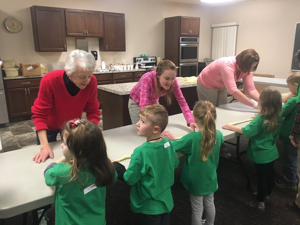 Vivian Krabill, Hannah Thomas, and Kristy Shillig helping members of the F.R.O.G. program make twist pretzels at the Evangelical Friends Church (Alliance, OH). -