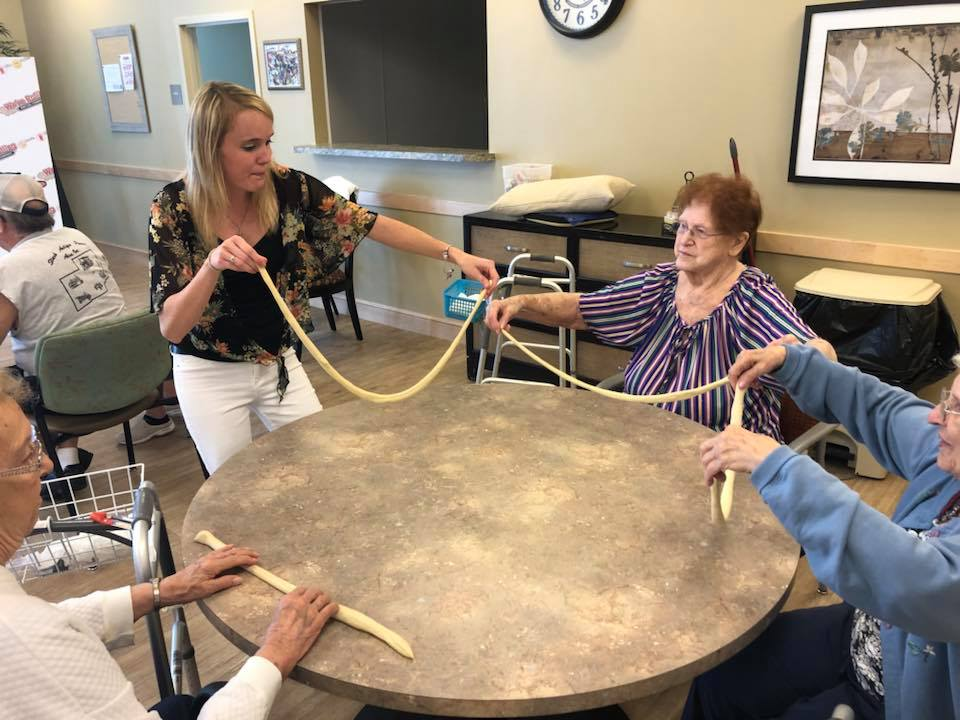 Hannah Thomas helping a few of the residents make twist pretzels at Danbury Senior Living. -