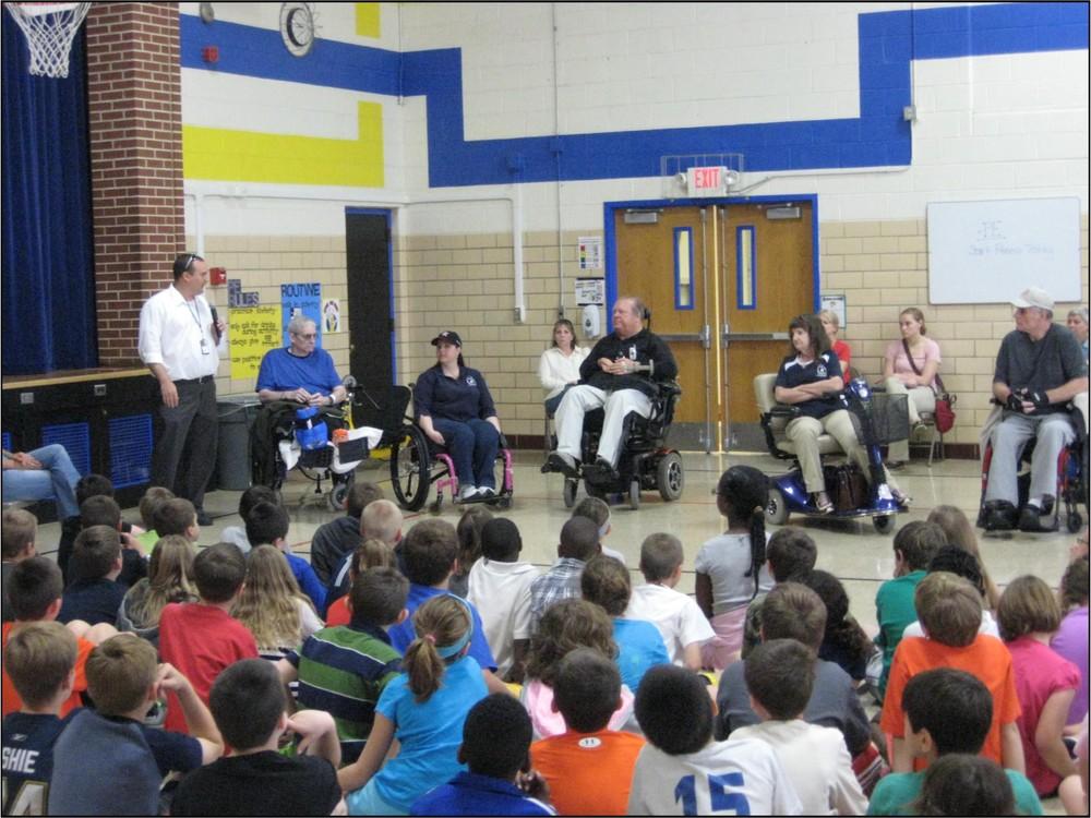Matt tells the children about wheelchair games.jpg