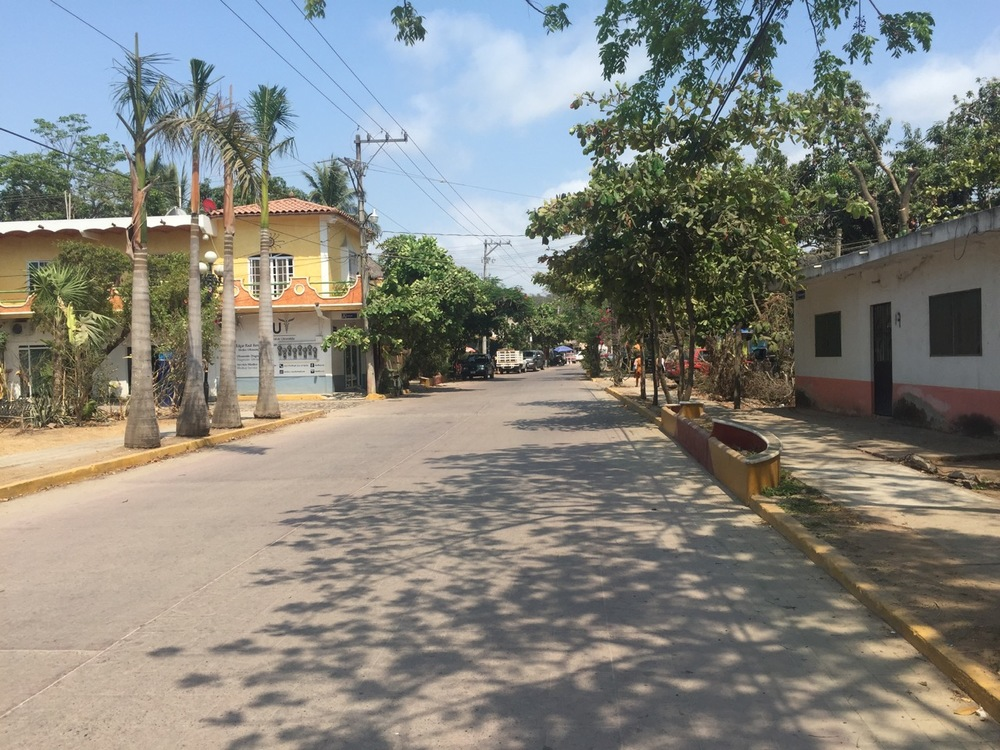 The bustling main road in San Pancho, Avenue Tercer Mundo, looking southeast.  The sole doctor's office in town is on the left.