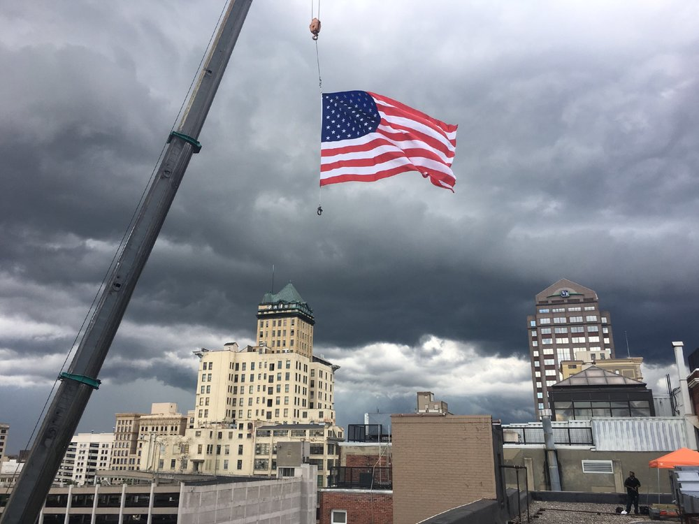 The industrial crane arrived yesterday to load building supplies onto the roof of the 124 Building. After all the work was done, our team hoisted a larger-than-life American flag in honor of our nation's Independence Day.