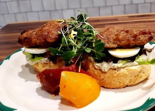 The Farmboy is herb aioli, tomato, fresh greens from Foxhole Farm, a hardboiled egg, and housemade sausage on a buttermilk biscuit