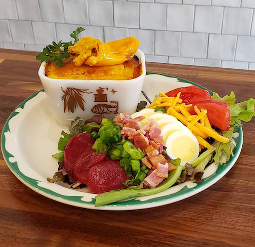 Warm Pork Chili Cornbread Pie topped with a melted cream cheese stuffed mini sweet bell pepper served with a small Cobb salad and buttermilk dressing