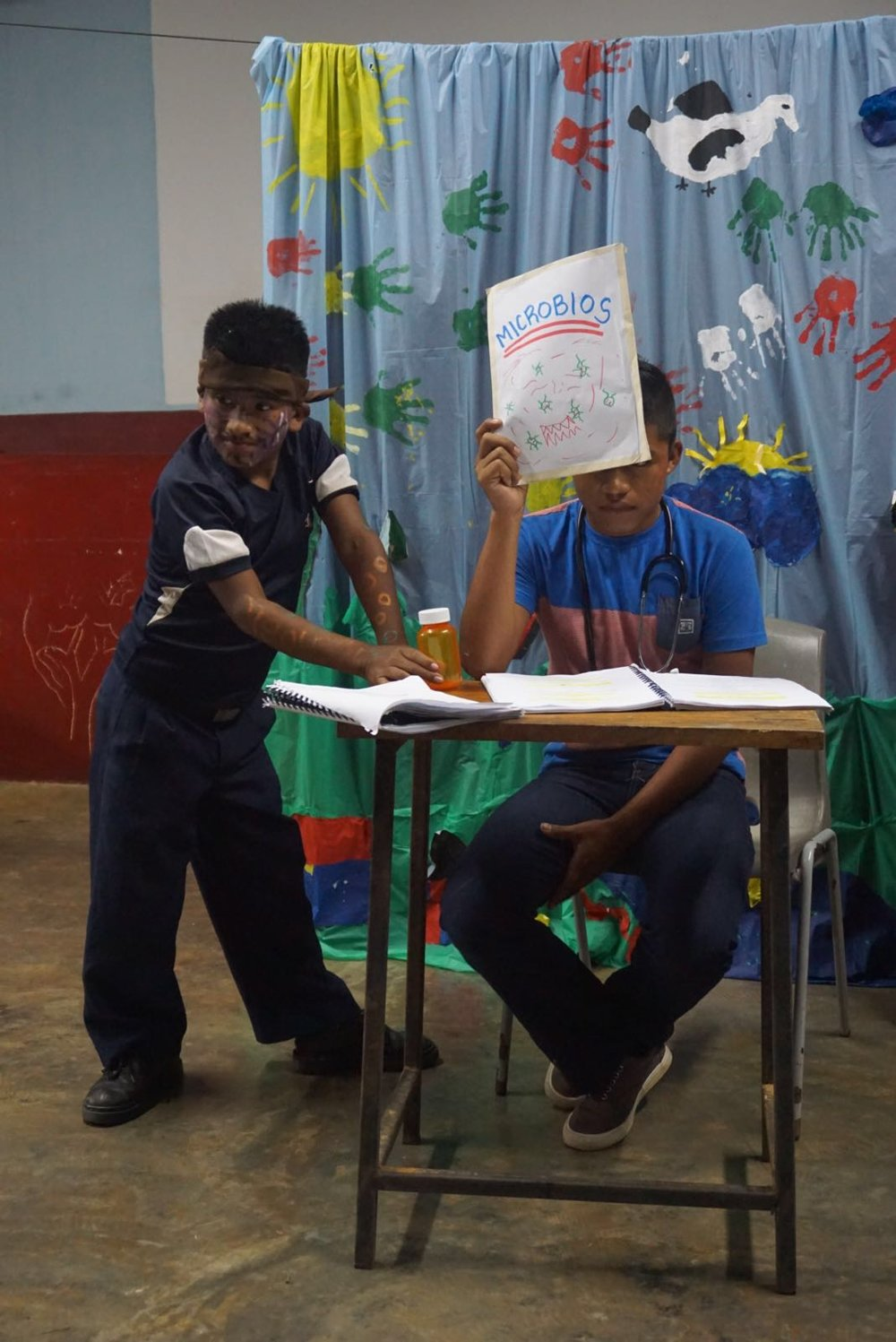 "Youth participants rehearse their scene. The student on the left is portraying a germ named ""Valentino Matasanos"". Translated, this name means ""Valentino Health Killer""!"