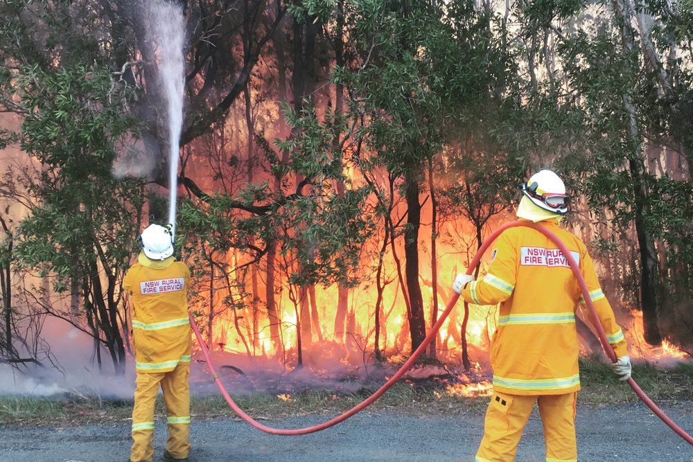 Pictured: Firefighters hard at work in extreme temperatures protecting the homes and properties near Lennox Head last week.