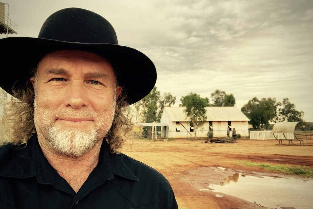 Pictured: Steve and the corrugated iron Lutheran mission church at Haasts Bluff in the western desert NT.