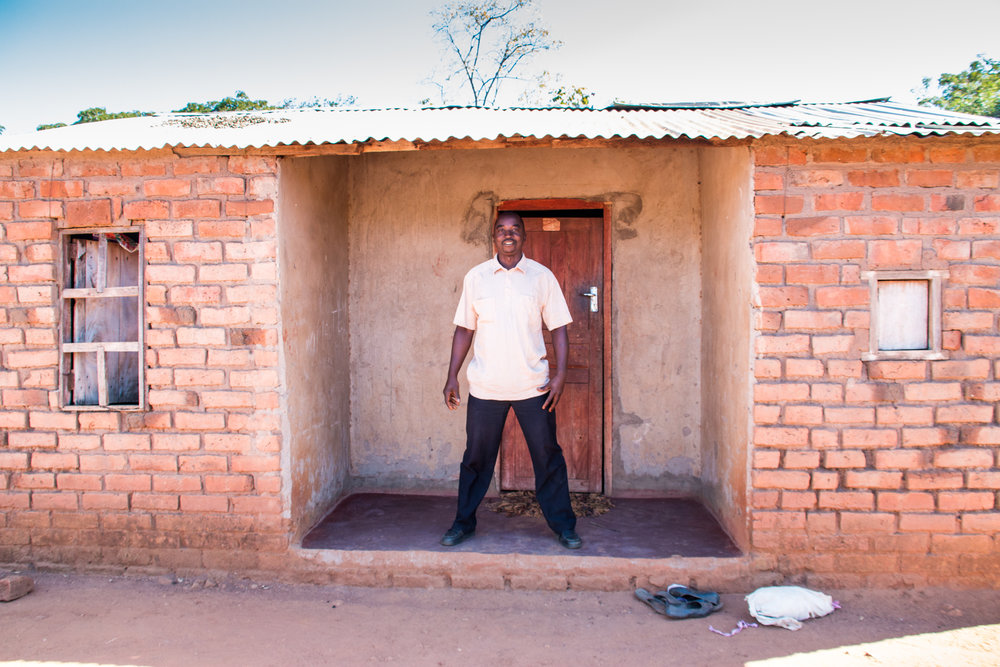 "Samson Tembo has been growing with Good Nature for 2 years - outside his new property, built with profits from growing cowpea. ""Last year, I bought two cattle, six bags of fertiliser and paid all school fees for my children."""