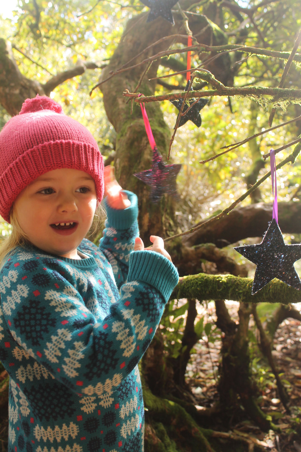 Fairies left some stars in trees for Mabel! Here she's wearing the Vintage Pink Otto Bobble Beanie and the Kingfisher Portcullis Jumper.