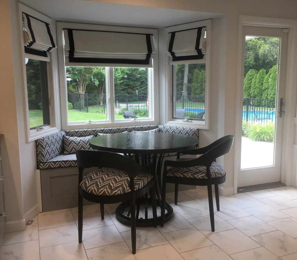 Custom window seat and coordinating chairs for comfortable family dining in this East Northport kitchen. beautiful custom mock roman shade valances to complete the relaxed yet sophisticated style.
