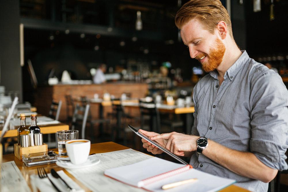 Man on tablet in café