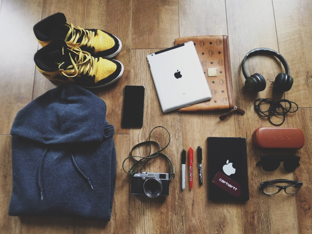 Kicks : Air Jordan 1 ; Grey Hoodie : Russell Athletics (Beware a guy that doesn't wear one ahah); My Ipad and his MCM pouch ; Monster Headphones ; Of course my Iphone 6s Plus (My mobile office) ; Fuji X100 : My point and shoot camera follow me everywhere (needs an update tho), Pilot ball Frixion, Sharpie Fine point, Pilot sign point, they are my pens ; My moleskine (3 years following me this one) ;Komono sunglasses and YSL glasses.