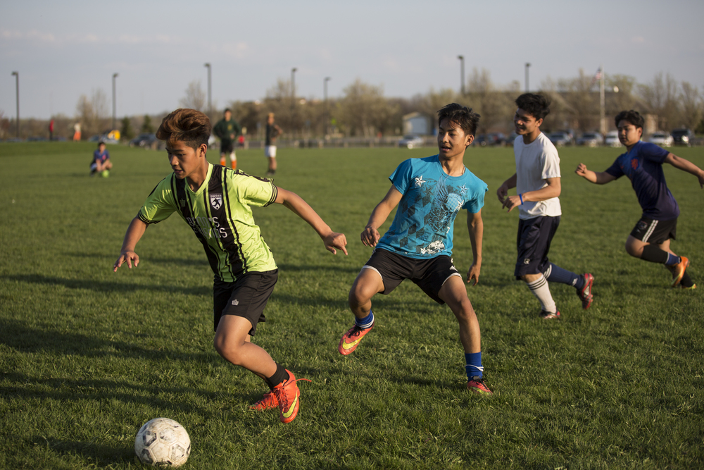 (from left) Hla Ku, Ehlerh, Eh Ku, and play in a scrimmage at practice at Buckland Park in Brighton, N.Y.. Ehlerh tries to run drills, but most of the boys fool around during these so scrimmages keep the boys more focused. May 3, 2015.