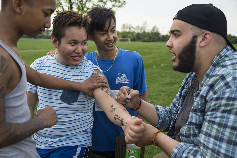 Josh Quarles (right), Ehlerh Htoo (second to right), and Hsar think of Karen profanities to write on Kong Si's arm using a tube of eyeliner they found at Buckland Park in Brighton, N.Y.. Josh is a librarian in Rochester and through helping many refugees at the library has become a part of the Karen community. May 10, 2015.
