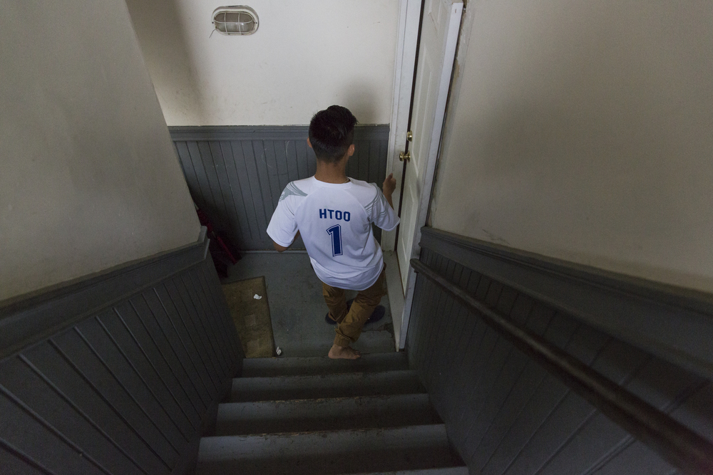 Ehlerh walks down the stairs to the lower level of the duplex to his brother's room to wake up his friend. Many of Ehlerh's friends sleepover on the weekends and end up staying in his brother's room because he has a bigger bed. May 16, 2015.