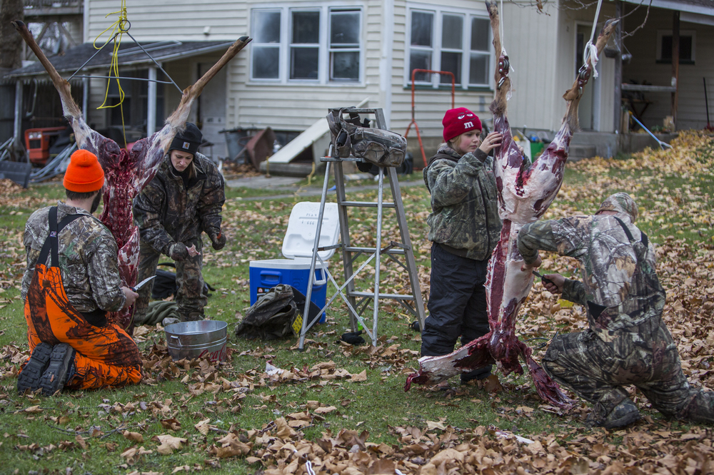 "(Left to right) Cory Rogers, Bridgette Pattison, her daughter Destinee Pattison, 10, and her husband Luke Pattison work together to trim the fat on Cory's first kills of the season in the Pattison's backyard in Lima, N.Y. ""For us, it's not about who gets the biggest deer or who gets the most deer,"" says Bridgette, ""it's ya know how long can this feed us for?"" Nov. 16, 2014."