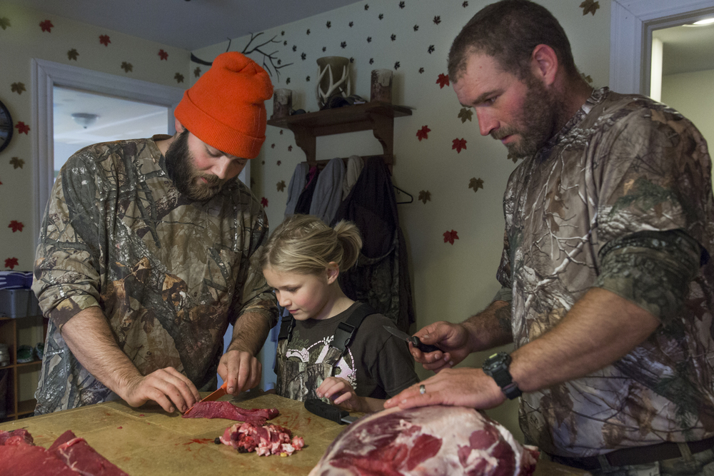 Cory (left) shows Destinee how to cut up the deer meat as her father Luke looks on. Destinee was in charge of cutting the deer meat into small pieces that will be packaged to freeze later. Nov. 16, 2014.