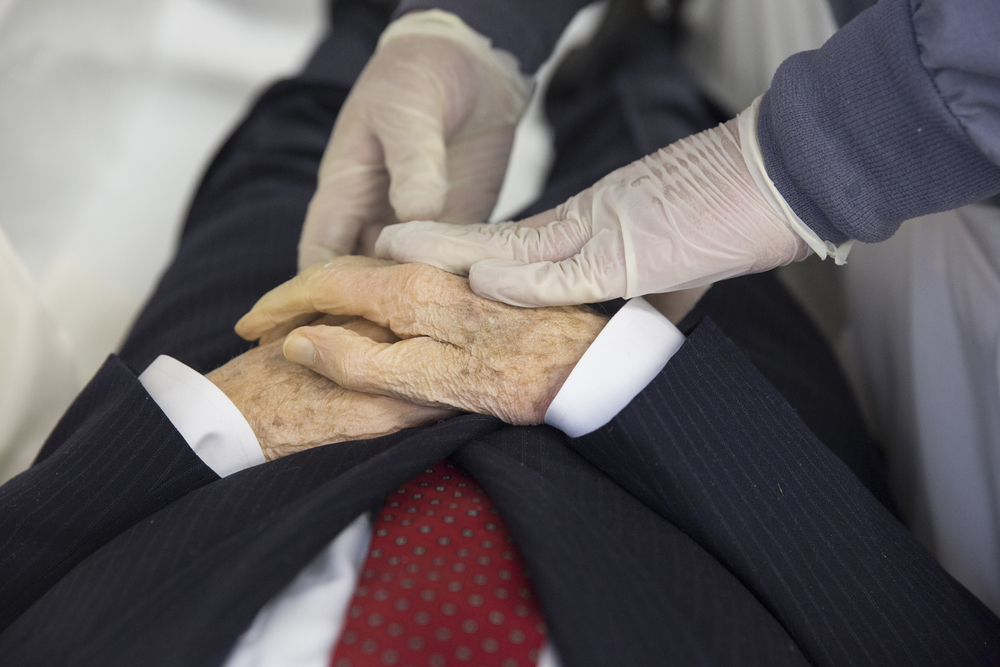 "A licensed funeral director (name redacted) places one hand of the deceased on top of the other during the final preparations for a funeral ceremony at a local funeral home (name redacted) in Rochester, NY on Feb. 18, 2015. ""If the hands are not placed in that position soon after death, it can be very difficult to place them there later."""
