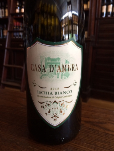 "Casa D'Ambra Ischia Blanco 2015     Our featured wine is a beautiful wine from a stunning place, Casa D'Ambra Bianco from Ischia, an Italian island off of the coast of Naples.     Winemakers on Ischia (eé-skee- ah) have been given the nickname ""Crazy Angels"" for their dedication to pursuing viticulture amid challenging factors both geographical and socio- economic. The D'Ambra Family can trace their wine making lineage back to 1888 when Francesco D'Ambra started producing wines on the island. The wines have always been successful in the local Neapolitan market and we are fortunate today that we can get them in the US.     The Ischia Bianco is unique and has an individual expression, produced from the indigenous varieties Biancolella and Forastera.   The first thing you notice about this wine is how intensely aromatic it is, upon pouring beautiful floral aromas leap out of the glass. There is a surprising fullness on the palate with notes of firm nectarine and orange fruits followed by a dry mineral finish that recalls aspects of the open sea. This profile makes it a perfect partner for rich seafood that has some texture, such as crab, lobster, and shellfish.     Purchase a bottle during the month of August and save $3 off of the regular price, now $13.99"