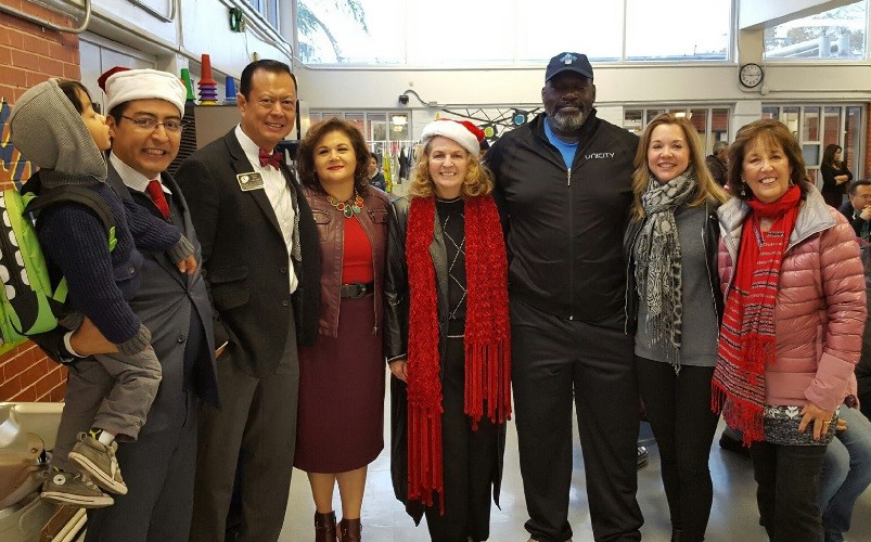 Neff ECC Principal Leal, Rotary Club Governor Eric Liu and wife Sandra, First Book of Greater Houston Director Sheila Long Armstrong, former NFL player Charles Davis, Dr. Julie Baker Finck and Ladies for Literacy Guild Member Patti Gillies line up to help distribute bicycles.