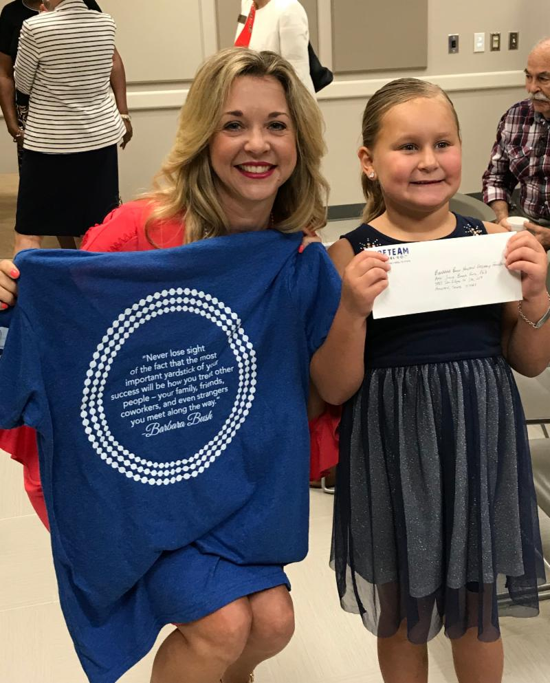 Philanthropic six-year-old Kole Barton presents funds she raised by selling t-shirts in honor of Mrs. Bush.