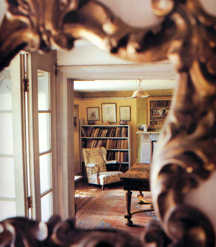 The nineteenth-century Italian gilt mirror in the hall reflects a view of Clive Bell's study through the open door.