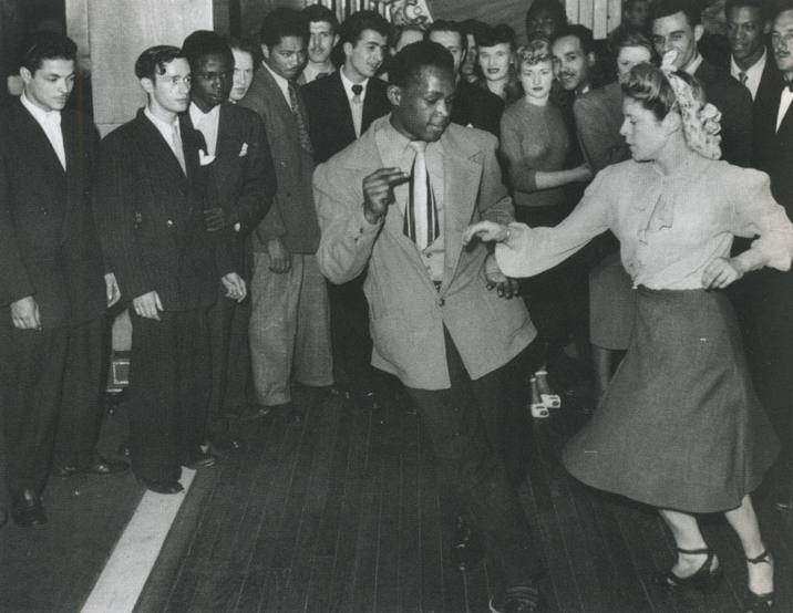 Night clubs and dance halls were humming throughout the war. Here, a black US serviceman in civvies teaches his partner to jitterbug.