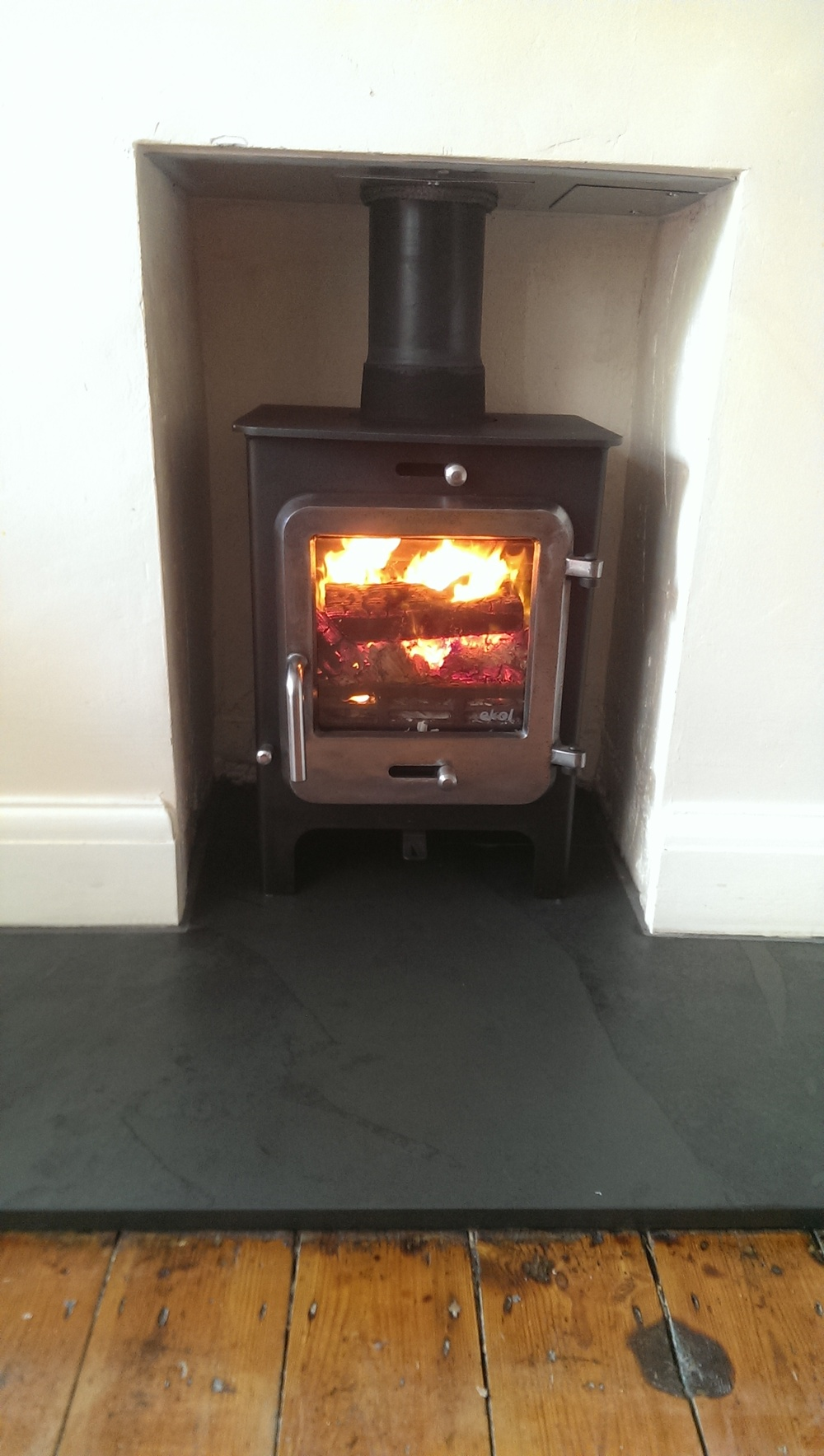 Ekol Clarity 5kw multi fuel stove with burnished door on a riven slate hearth