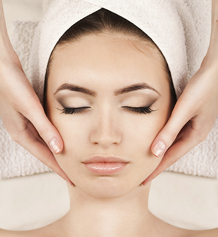 Portrait of young woman receiving facial massage at day spa