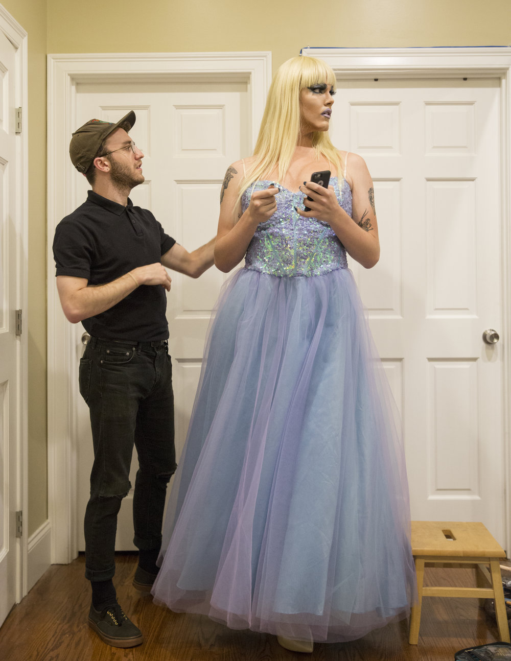 "Mount's boyfriend, James Richardson, 24, of Boston, inspects the handiwork on his partner's dress. Mount hemmed his dress down from a women's size 24 to fit his masculine frame. he describes his apparel as a ""Frankenstein dress."