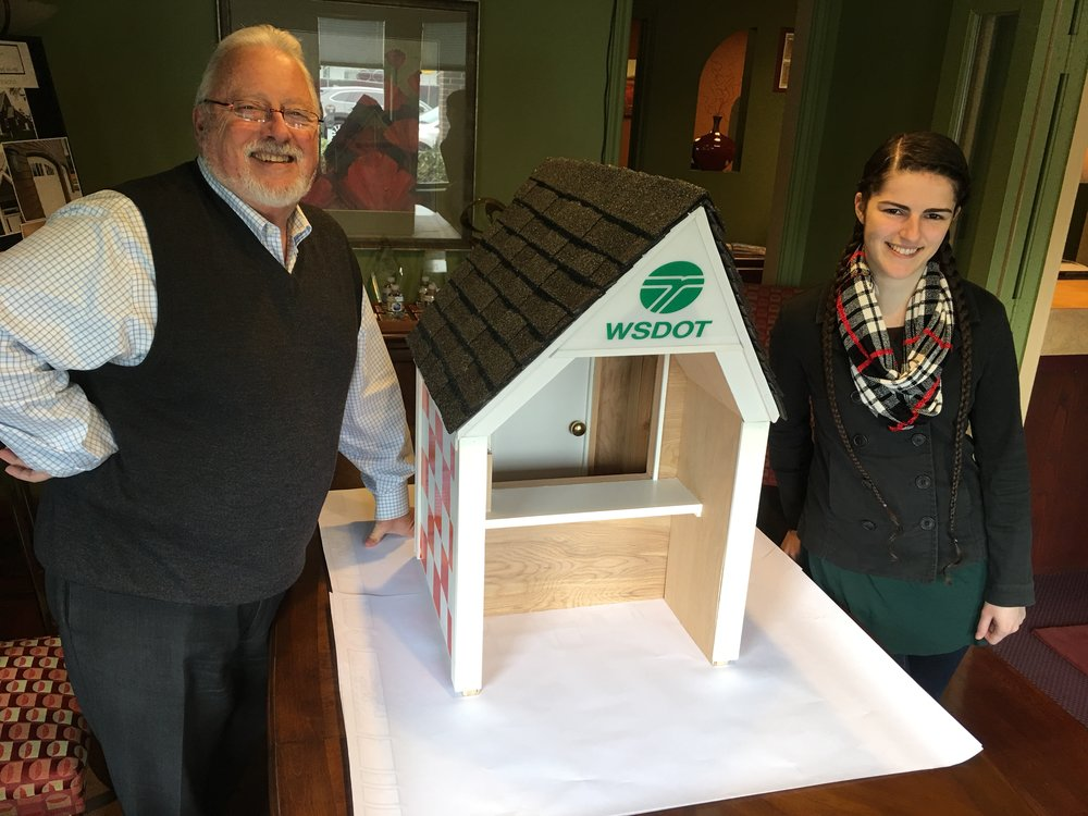(from left) George Welsh and Hannah VanGelder stand next to their small scale-to-size winning Washington state airport kiosk design prototype on Tuesday, February 27, 2018. Welsh is a residential designer and VanGelder is a freelance artist. Both are from Vancouver, WA and said they are happy their design won and look forward to seeing their design come to life at Washington state public-use airports.