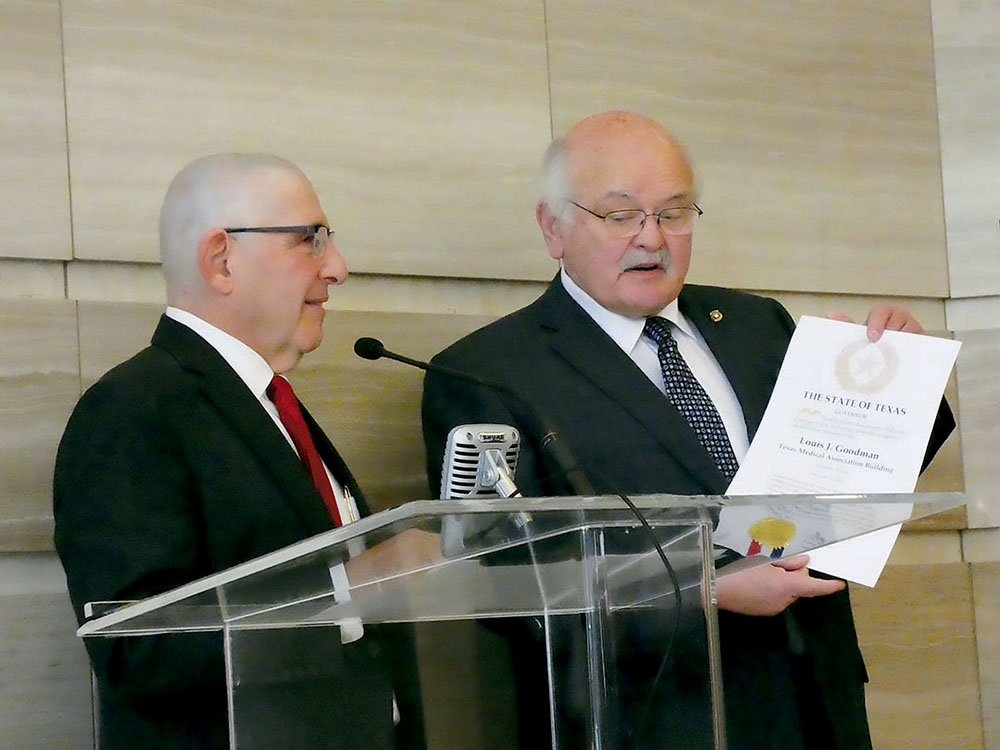Texas Medical Association President Doug Curran, M.D., presents TMA CEO Louis J. Goodman, Ph.D., with the proclamation from Governor Greg Abbott affirming that the TMA building will now be known as the Louis J. Goodman Texas Medical Association Building. Credit: Steve Levine