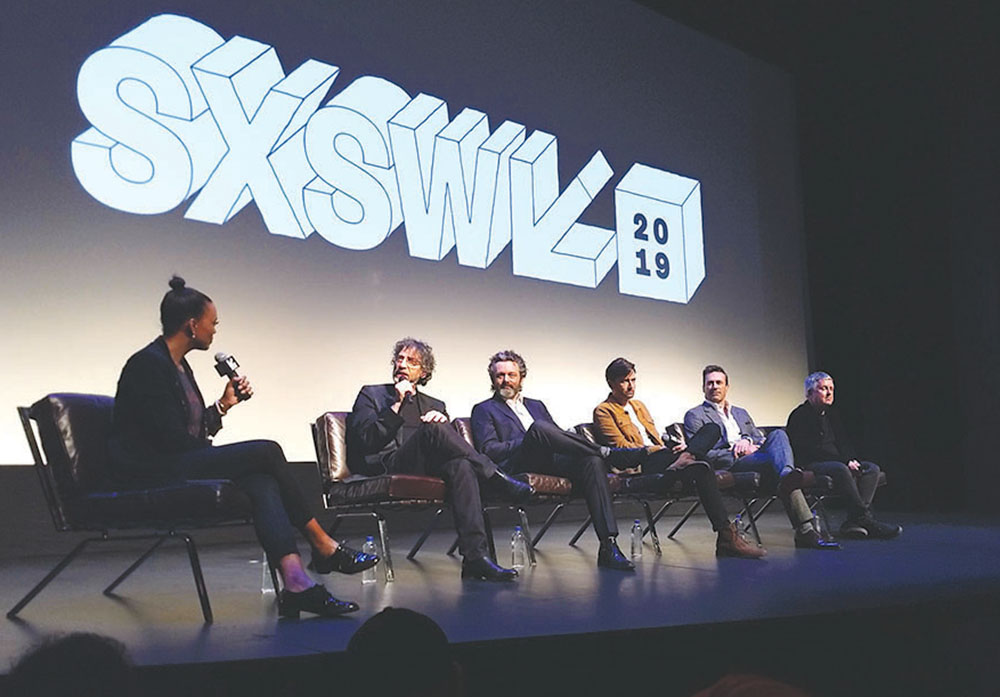 """Author Neil Gaiman discusses adapting his book, """"Good Omens,"""" into an Amazon Prime show as part of a March 9 panel that included director Douglas Mackinnon, cast members Michael Sheen, David Tennant and Jon Hamm, and panel moderator Aisha Tyler. Credit: Tonyia Cone"""