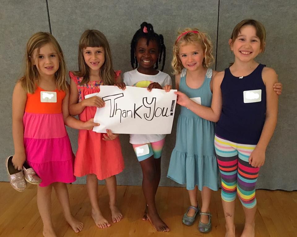 """Arts Together students holding a sign that says """"Thank You!"""""""