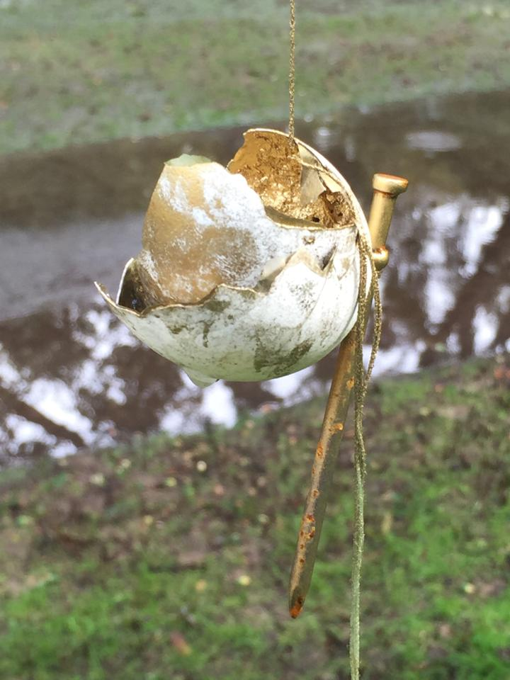 """Egg Bell,""  photograph of an installation, part of Lapthisophon's project, ""Toccare (Non) Toccare"" at The Nasher Sculpture Center, 2015, rope, string, egg, nail, and gold pigment  [Image Description: A broken eggshell hangs suspended in the air, a nail attached to one side of it. The outside of the broken shell appears to be smudged with dirt. The inside of the shell and part of the nail are covered in gold pigment.]"