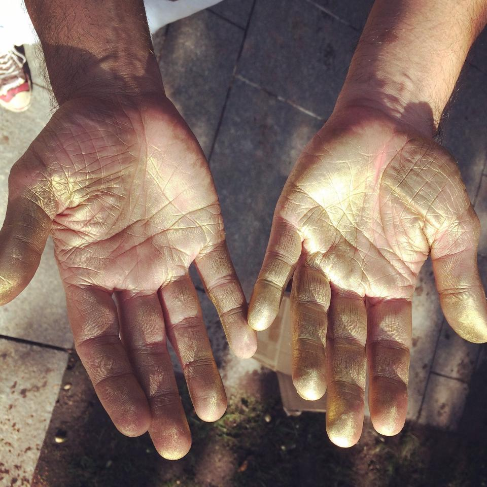"""Untitled (hands with gold pigment),""  photograph, 2015  [Image Description: A photograph taken looking down at a man's open hands, both palms up, smudged with gold pigment. The ground, pavement and part of a foot in a black, white, and red sneaker are visible beneath the hands.]"