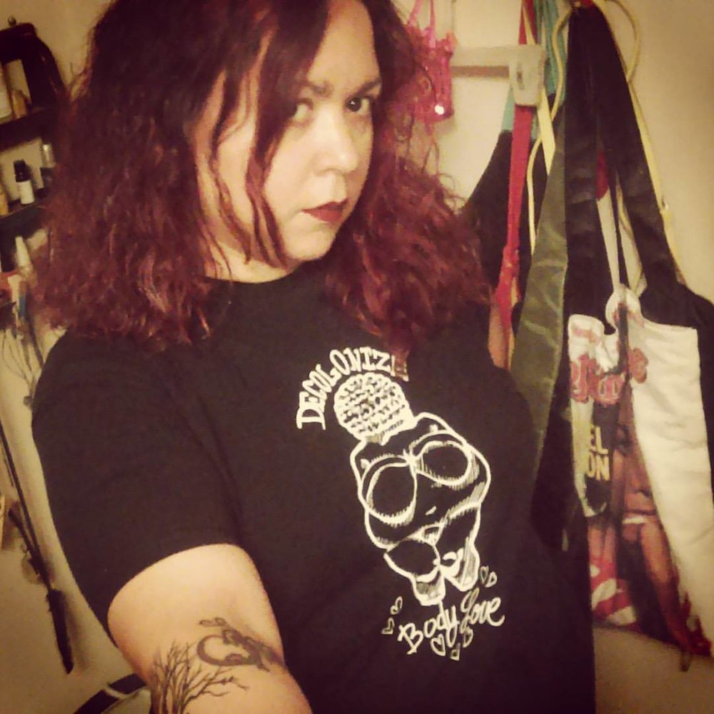 "A selfie taken by the poet, it shows the femme person, a Chicana/Boricua brown person, who is not smiling, with dark red & black curly shoulder length hair, wearing dark red lipstick and a black t-shirt that reads ""decolonize-body love"" with an image of a fat femme person. Noemi's arm is tattooed with a heart and tree branches and her arm is outstretched, holding the camera."