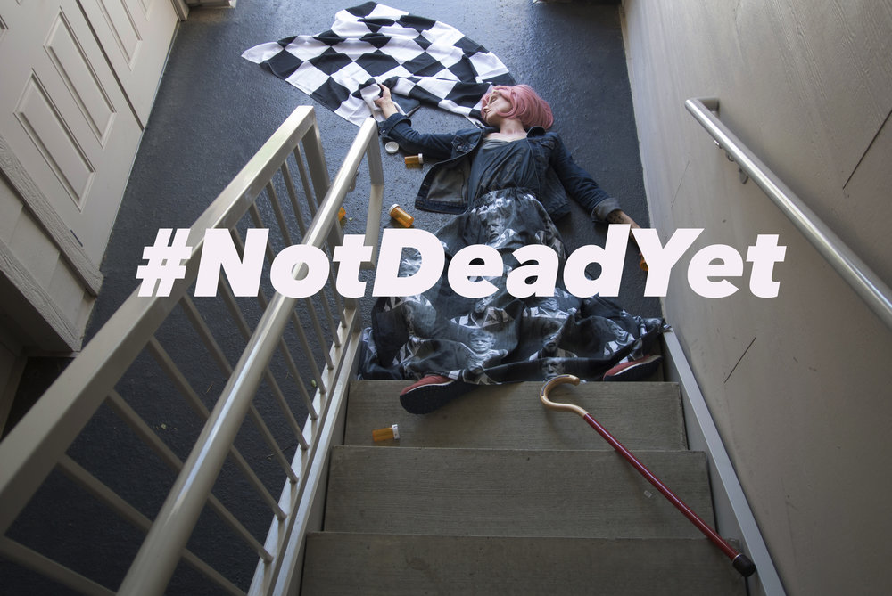 Karrie lies at the bottom of steep, concrete stairs as though she has fallen backward. Her feet are partially on the stairs, and her body is twisted. In her right hand, she grips a NASCAR checkered racing flag (signaling both the start of a race and the winner crossing the finish line); in her left hand, an empty prescription bottle. Her red walking cane appears to be falling down the stairs after her. Red in NASCAR signifies the race must be stopped immediately, usually due to danger on the track. Karrie is wearing a skirt printed with her brother's police booking photograph. The photo is overlaid with white text that reads:    #NotDeadYet