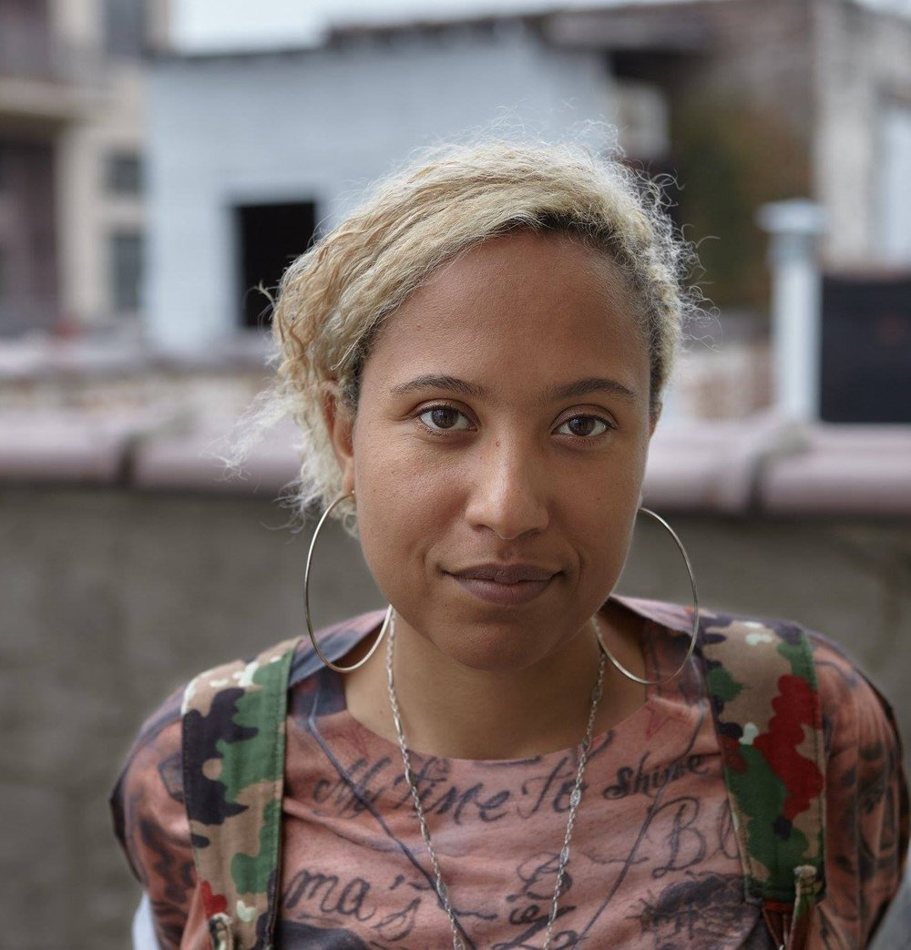 A black Haitian person in a pink shirt and a multicolored camouflage backpack, large gold hoop earrings, and blonde wavy hair looks directly at the camera. Photo by   Dan Gutt. Originally printed in RAGGA