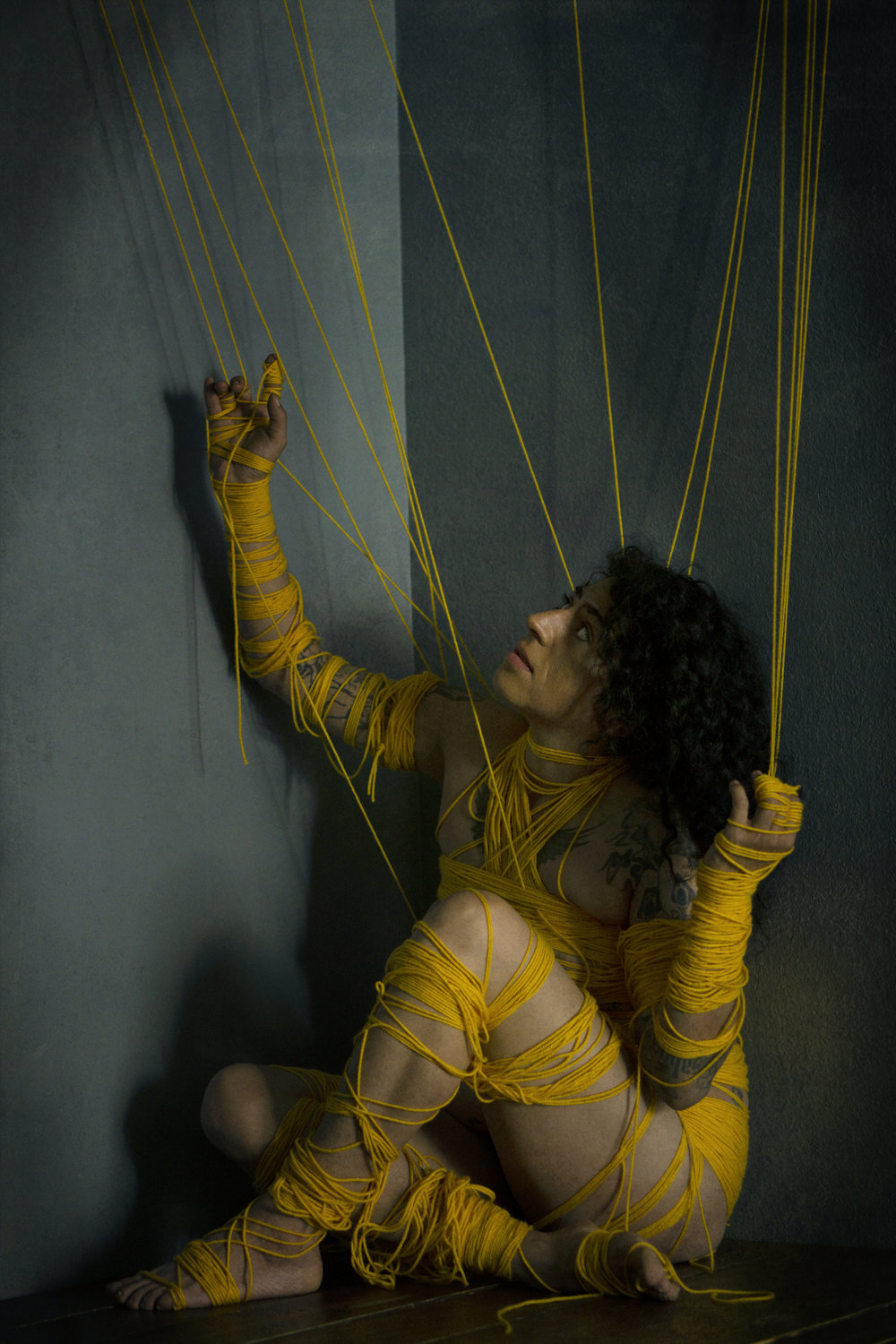 """""""Wrapped"""" by Kathryne Husk  In a cramped greenish-umber space, an long haired ambiguously gendered figure (slightly feminine of center) sits on the ground with one hand against the wall. The figure is wrapped tightly in bright yellow yarn/threads that hang from the top of the frame"""