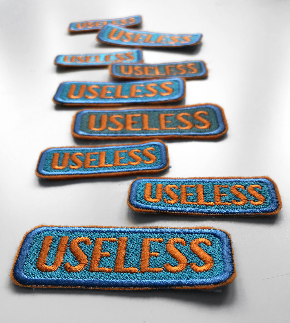 """Patches by Laura Cowley  An image of multiple sew on patches. The patches are bright teal rectangles with orange text saying """"USELESS."""""""