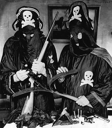 LAW ENFORCEMENT AGENTs posing with confiscated black legion costumes and weapons.