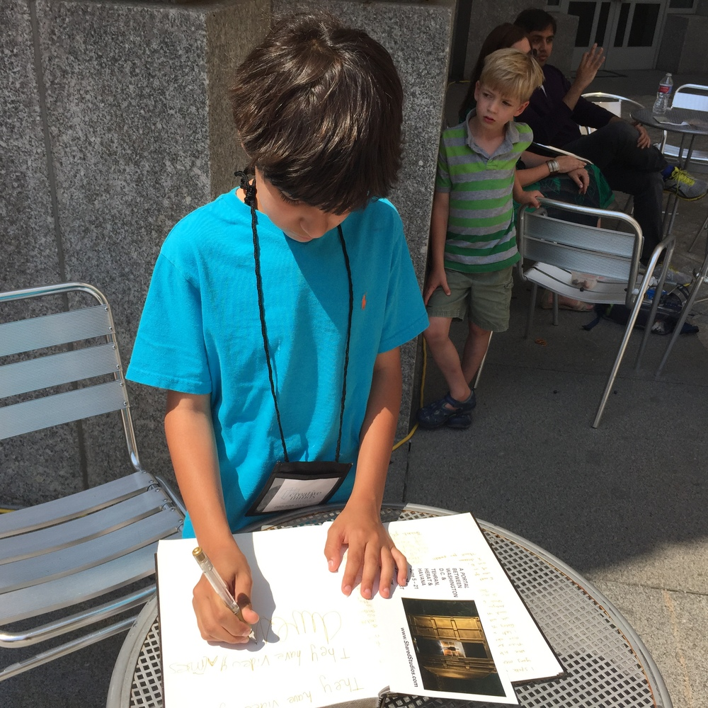 Child signing the gold book at the Woodrow Wilson Plaza