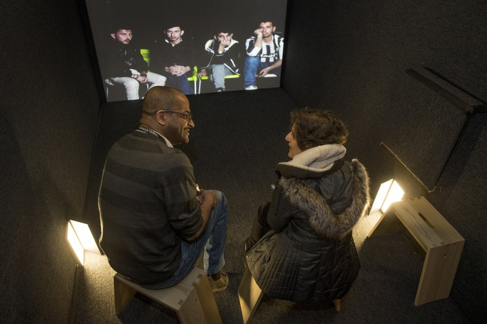 """Iraqi refugees in Erbil listen as Wassim Subie translates their words to Nancy Gillette at a video """"portal"""" at the U.S. Holocaust Memorial Museum that allows live, face-to-face conversations from across the globe. (Linda Davidson/The Washington Post)"""