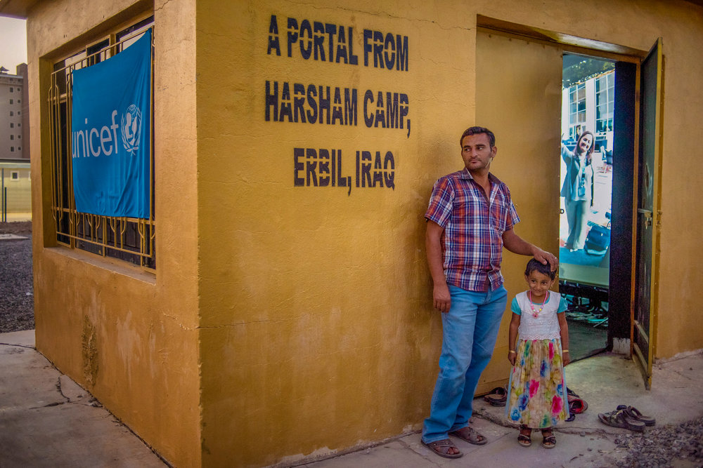 A father and daughter outside the Portal at the Harsham Camp for Internally Displaced Persons in Erbil, Iraq, connected to a Portal in Philadelphia, USA.  © UNICEF Iraq |  Download JPEG (3.6mb)